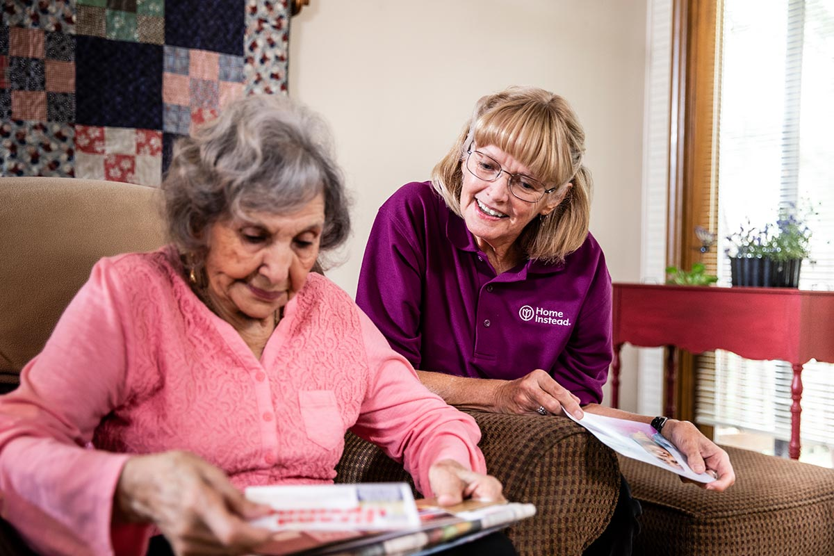 Home Instead CAREGiver and senior looking at mail