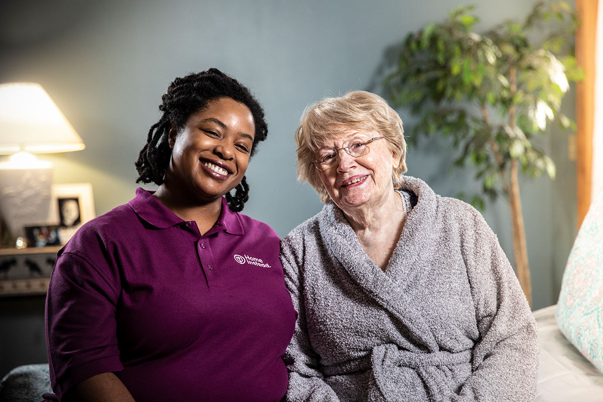 Home Instead Caregiver and senior woman smile while sitting together on bed at home