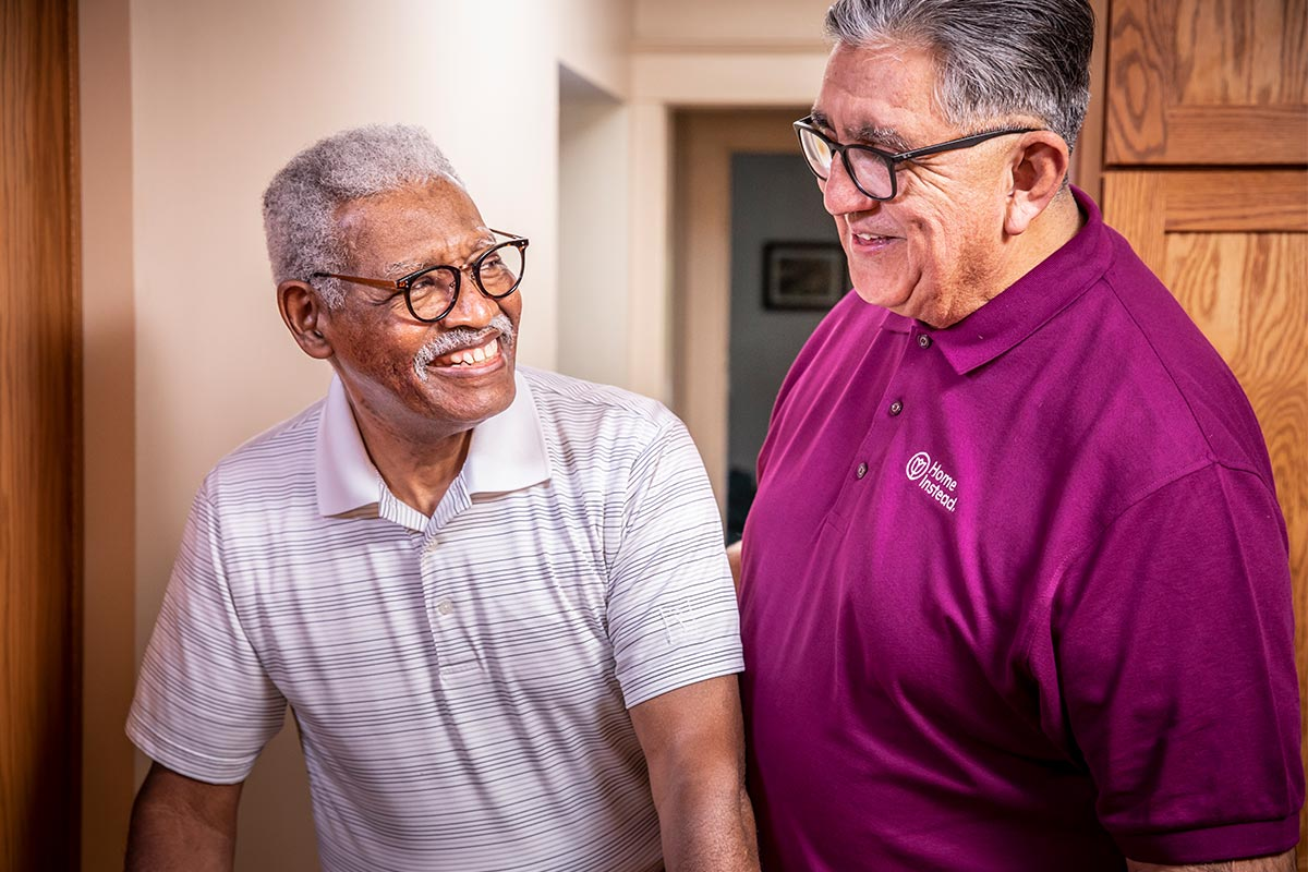 Home Instead Caregiver helps senior man walking at home and provides home care services near me