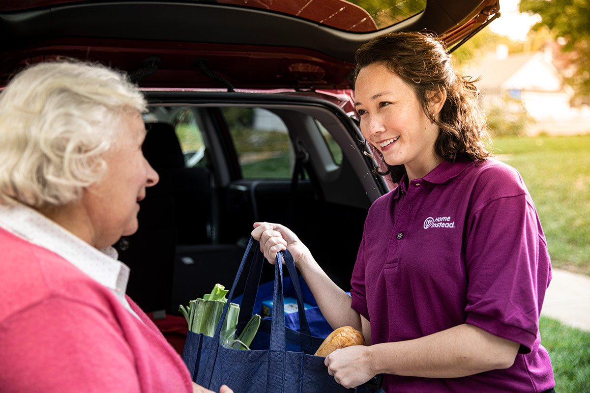 Home Instead Caregiver helps senior woman unload groceries from vehicle