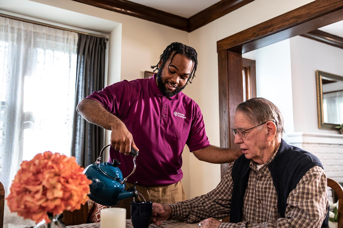 Home Instead Caregiver pours coffee for senior man sitting at home