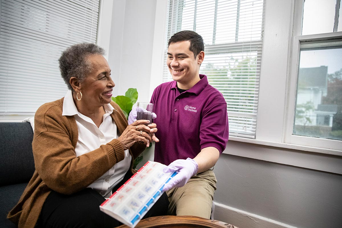 Home Instead Caregiver provides senior woman medication and water